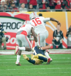 Irish junior linebacker James Onwualu holds onto the legs of Buckeyes sophomore quarterback J.T. Barrett during Notre Dame's 44-28 loss to Ohio State on Friday.