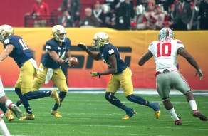 Irish sophomore quarterback DeShone Kizer, left, hands the ball off to freshman running back Josh Adams during Notre Dame's 44-28 loss to Ohio State in the Fiesta Bowl on Friday in Glendale, Arizona.