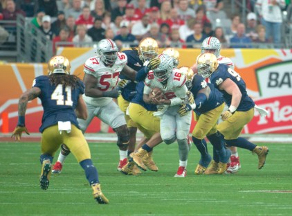 Notre Dame defenders swarm Ohio State sophomore quarterback J.T. Barrett as he scrambles for a gain during the Buckeyes' 44-28 victory over the Irish on Friday.