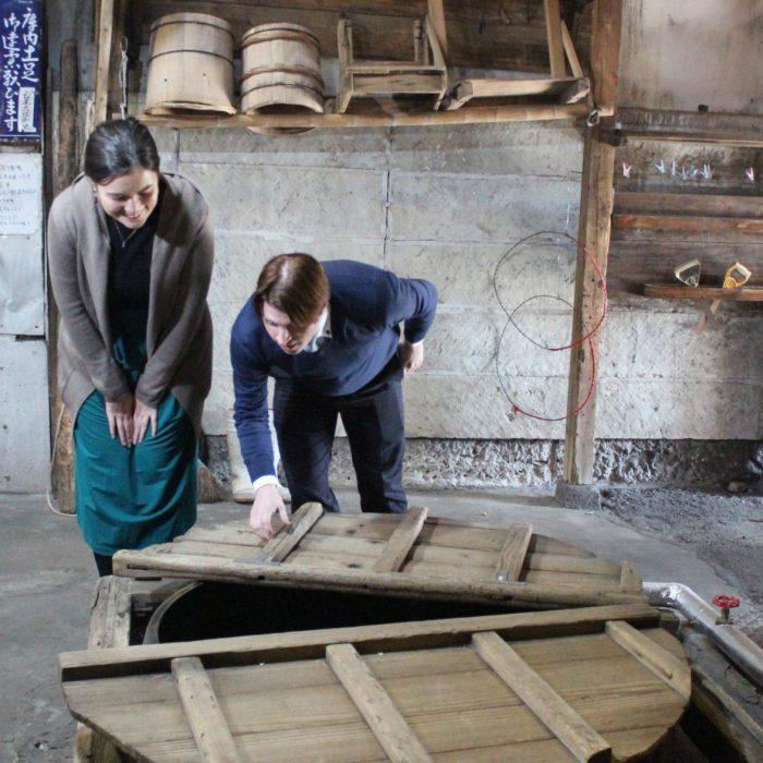 Visitors looking into the steaming vat at Katayama sake brewery nearby Tokyo
