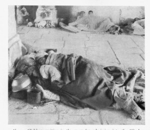 Two Unknown refugees sleeping on the floor, covered with a blanket.