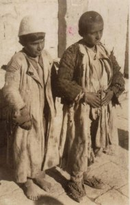 Two refugee boys dressed in scavenged clothing. The boy on the left is barefoot; the boy on the right wears shoes that are either improvised or severely damaged.