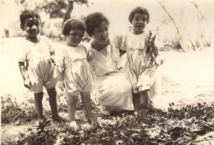 Nellie Mann with three children from the orphanage in Seydon Syria.  Mann,  kneeling embracing her three children who look happy and healthy. The four of them are in the woods.