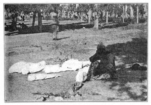 Mother with her dead children, the Armenian cry after the genocide. In the photo, the mother sitting down on the floor with her dead children wrapped in white cloths laying on the ground in the woods.