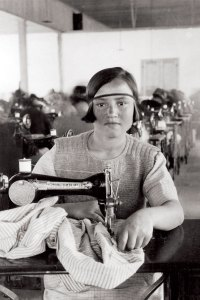 Young girl working at a sewing machine in an orphanage workshop in Syra, Greece. The orphans sewed clothing and linens for the orphanage and for sale in the community. All profits went toward the orphanage. This photograph also appeared in a Near East Relief promotional booklet.