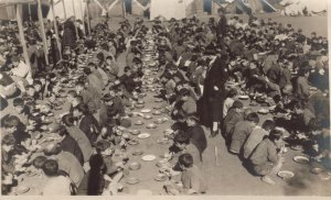 1400 orphan boys at a camp eating in tin plates. One relief workers and supervisors are supervising them.