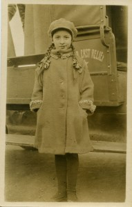 Girl in winter clothes standing in front of truck with Near East Relief insignia on the door.