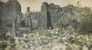 Soldiers (probably Russian) standing over human remains in a burned building. Many Armenians were deported to remote locations and massacred.