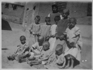 "The original caption reads: ""These are some of the small number saved from starvation. These little ones have not yet begun to gain flesh, but their digestion is recovered. I stood by the bedside of a dying girl with whom Dr. Little had worked for weeks exhausting all her meager facilities for recovering the health of the digestive organs.""