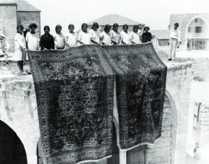Women and girls standing and holding handmade rug.