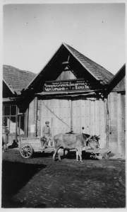 Man with a cow cart in front of a small building. The building sign, which is in both Armenian and Russian, announces that this is a library or reading room.