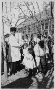 A man in a distinctive round black hat and white coat, and another adult in a similar outfit clip the hair of young children. The adults hold shears. There are tufts of hair visible on the ground. New arrivals at orphanages usually had their heads shaved to prevent the spread of lice (which carried typhus) and the contagious scalp disease favus. Probably Tiflis, c. 1920.