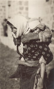 Mother carrying a child in the traditional Armenian manner. Nellie Miller's original caption reads:
