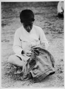 This photograph of a boy repairing a pair of trousers appeared in a Near East Relief publication with this caption: