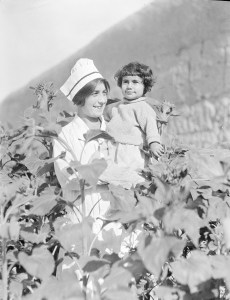 Nurse holding a child in the garden at Alexandropol. The nurse is probably a student or graduate of the Edith Winchester Nursing School at the orphanage.
