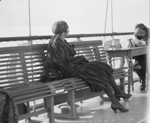 Unidentified well-dressed woman on a ship's deck. Based on her clothing, the woman is probably a relief worker or the wife of a Near East Relief worker. This negative is part of a series that includes views of refugees on a ship deck. Those photos were probably taken from this upper deck, looking down at the crowd.