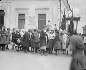 Girls with flags walking standing in front of a building with an ornately decorated canopy. The girls appear to be part of a parade. It is unclear if they are orphans, because they are not wearing matching uniforms.