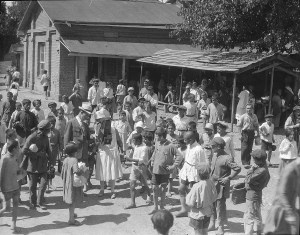 Barclay Acheson (in white hat) with a large group of children in front of a house.