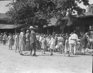 Barclay Acheson (in white hat) on the street with children. The woman at left is probably a relief worker.
