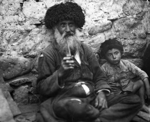 Old man with a young boy seated in front of a stone wall. Both wear traditional hats from the Caucasus region.