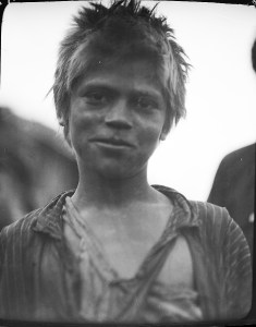 Informal portrait of a young boy wearing ragged clothes, including a torn striped shirt. Based on his light-colored hair, this boy may be a Russian refugee.