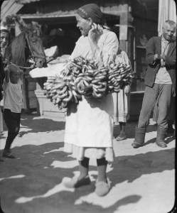Woman selling pretzels or some other type of twisted bread in an outdoor marketplace