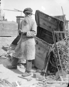 Bearded man in cap and glasses. The man wears and apron and stnds next to a large open trunk. A disassembled bedstead is nearby. The man is probably selling furniture.