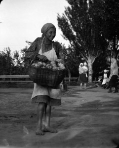 A smiling barefoot girl with a large basket of apples. The girl wears a headscarf and apron over a plaid dress.