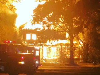 Photo shows fully engulfed house fire.