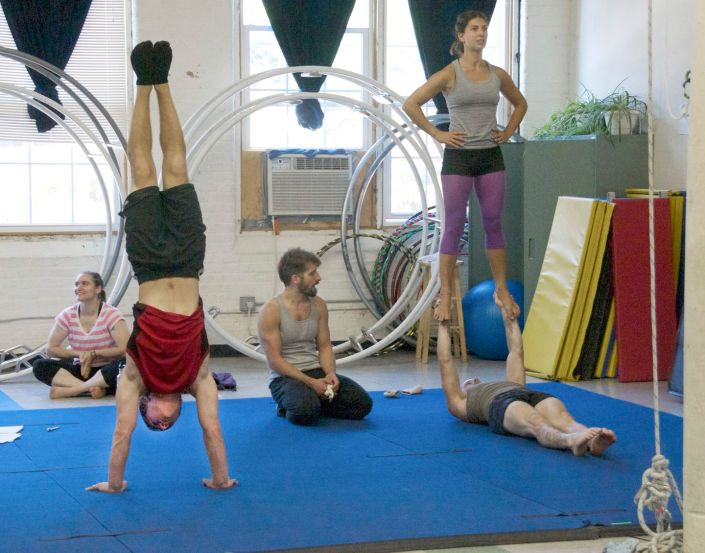 people training partner acrobatics with a coach at the NECCA studio in the cotton mill