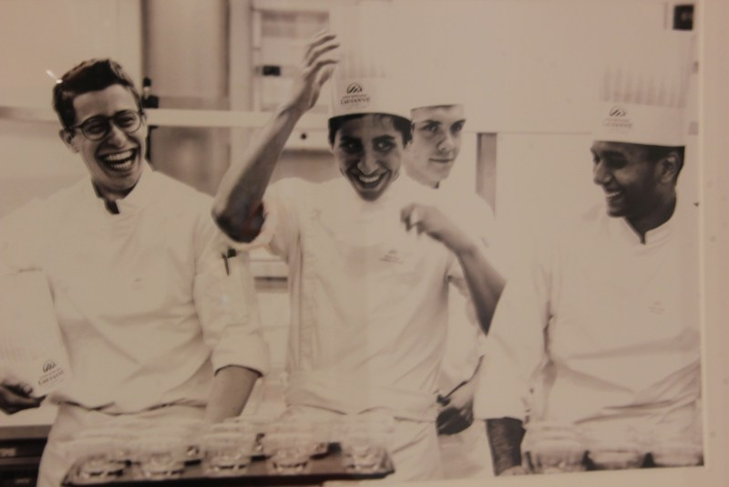 Photo is a black and white vintage photo of graduates at the start of EHL and depicts a group of four students in culinary uniforms laughing in a kitchen.