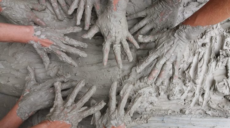 9 hands covered in mud