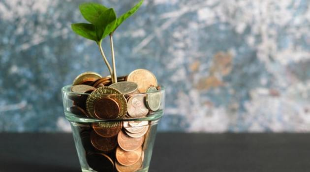 a glass cup filled with coins and a small plant growing from the cup
