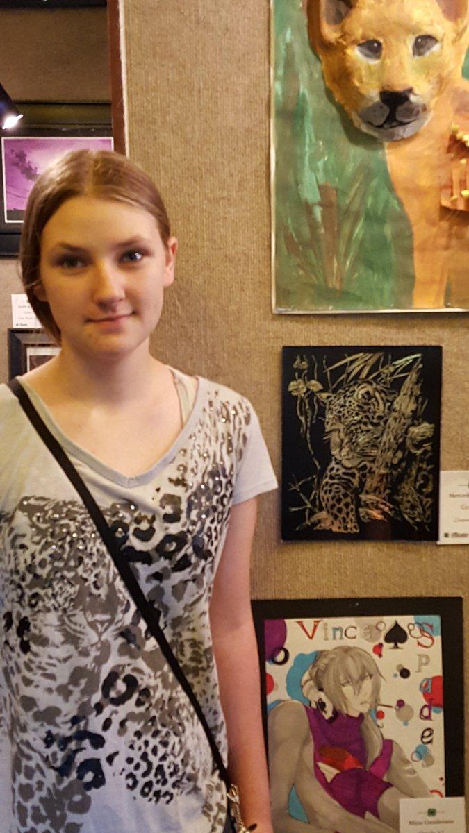 teen girl wearing jaguar leopard shirt standing in front of jaguar scratch art at art show