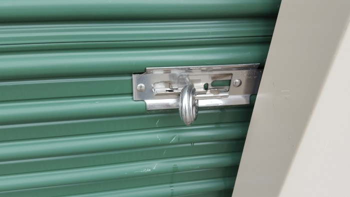 a circle lock on a storage unit but the door is unlocked because the metal slider was not slid to the right How To Keep Your Storage Unit Items Safe