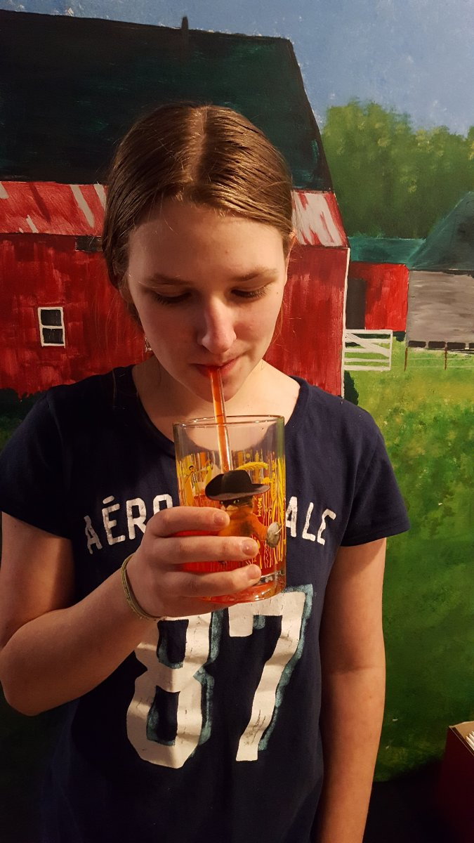 a teen girl drinking from a glass straw out of a glass