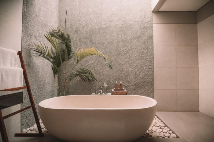 stone bath tub wood towel rack large palm plant tile shower stones around tub your bathroom dripping in luxury