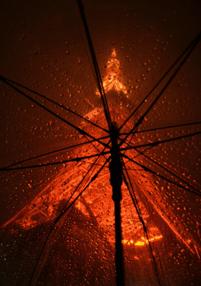 inside of an umbrella with raindrops on it looking up at a high lit structure seeking peace when you've sprung a leak in your roof