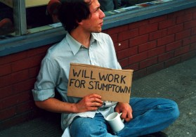 """Raymond holding a signs that says """"WILL WORK FOR STUMPTOWN"""" - part of an early art project."""