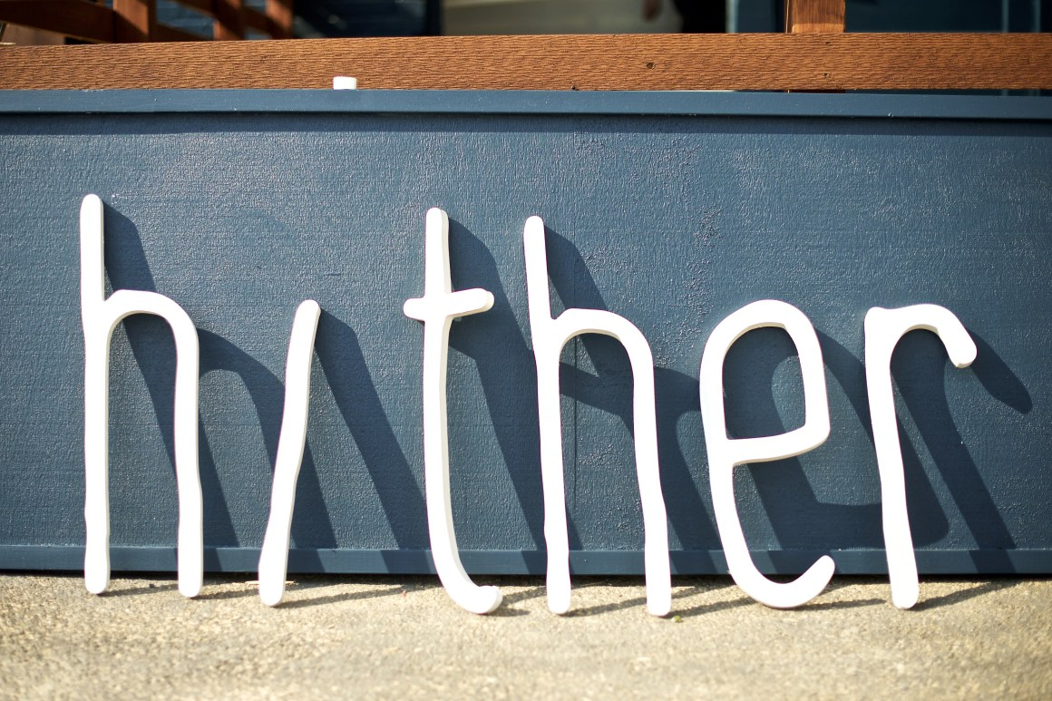 All the letters from the Hither Coffee + Goods sign leaning against a wall