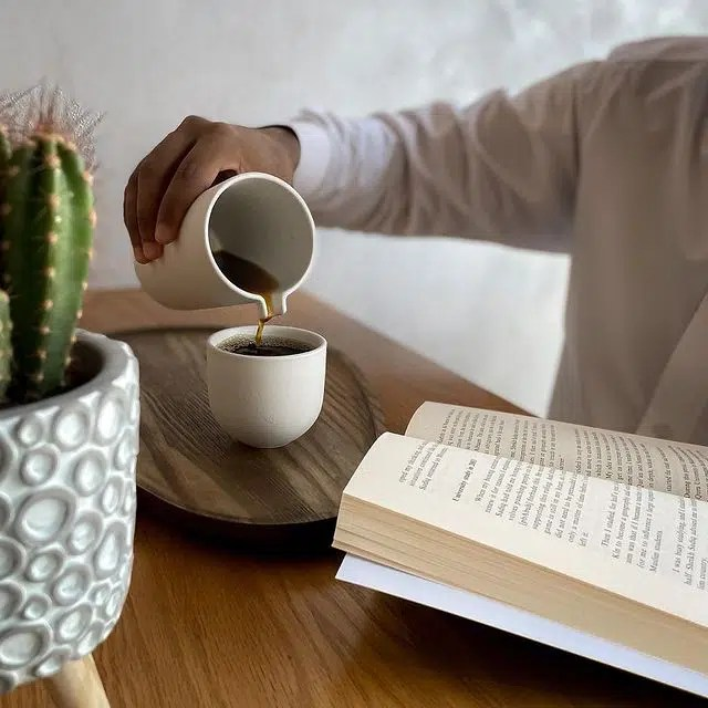 Person pouring coffee and reading a book at Stanza