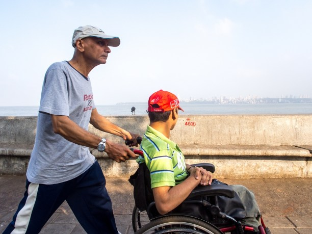 4010: A father and son in a red wheelchair with red cap on the morning walk.