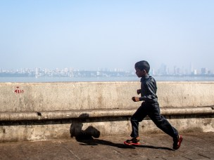 A young excited kid with red floaters on runs to have closer look of the sea probably for the first time..