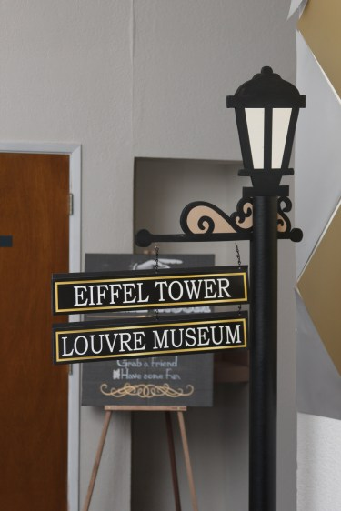 Pre-printed signs mounted on foamcore board and hung on chains give the wood lamp post more charm