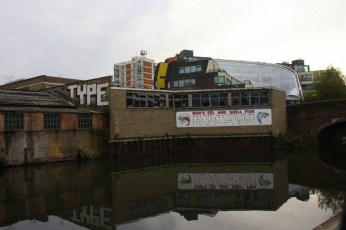 An abandoned warehouse with the new boat-like structure of Bridge Academy behind. The school, built in 2008, has won awards for its design, which attempts to provide adaptable classrooms and to deter bullying.