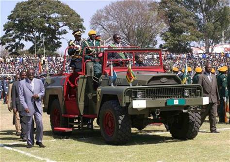 Mugabe riding on a Chinese made military vehicle