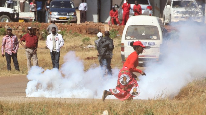 A woman ran past teargas as opposition party supporters clashed with police in Harare. Credit: Reuters