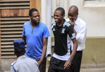 The accused police officers with an unidentified man after their court appearance in Bulawayo