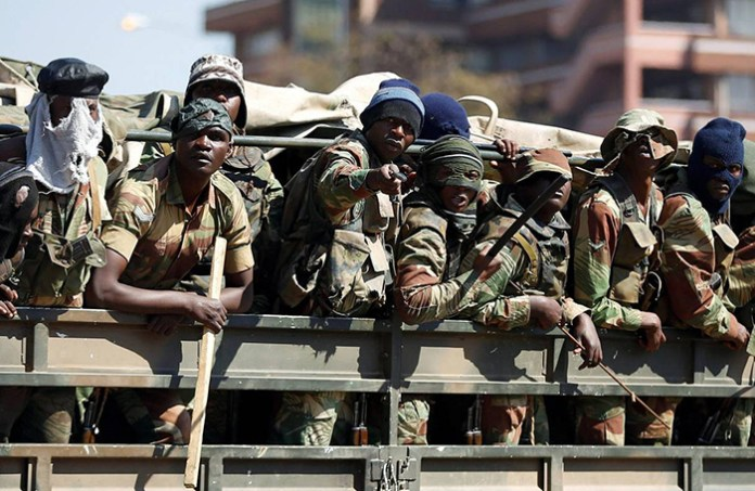 Members of the military gesture to the photographer as they patrol the streets of the capital Harare, Zimbabwe (REUTERS/Siphiwe Sibeko)