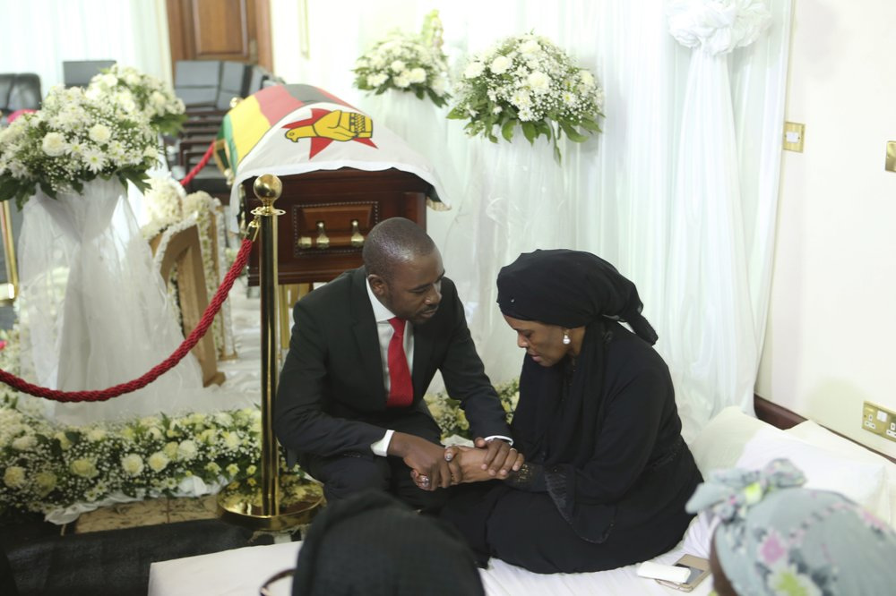 Nelson Chamisa, left, leader of the main opposition party in Zimbabwe, consoles Grace, wife to former Zimbabwean leader Robert Mugabe at his residence in Harare, Thursday Sept. 12, 2019. Zimbabwe's founding leader Robert Mugabe made his final journey back to the country Wednesday, his body flown into the capital amid the contradictions of his long, controversial rule. (AP Photo/Tsvangirayi Mukwazhi)